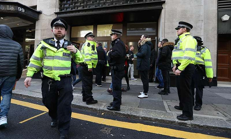 Police officers are seen outside the office building housing Sony Music's offices in London. —AFP