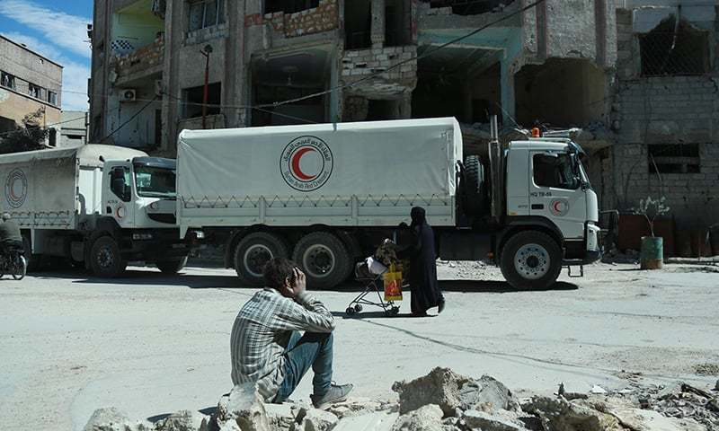 Syrian Red Crescent trucks carrying humanitarian aid in a rebel-held Syrian town. — AFP/File