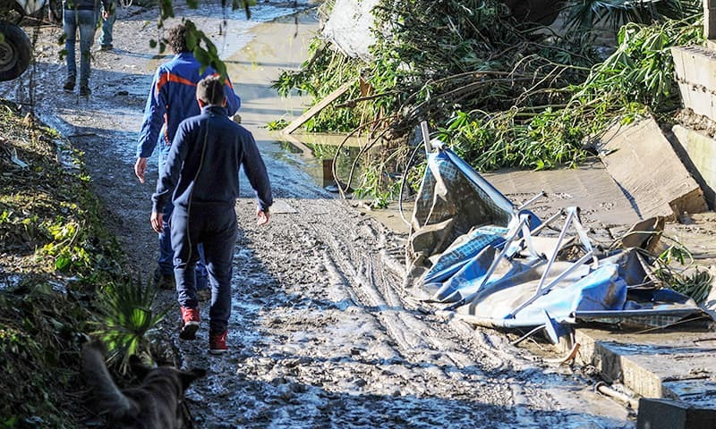 People pass by damages on a flooded road near a house where nine people of the same family died after a small river burst its banks on the southern Italian island of Sicily. —AFP