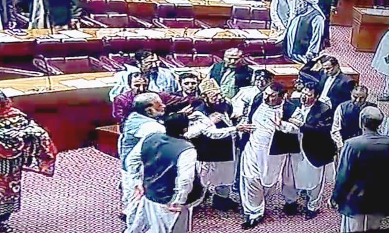 Lawmakers prevent PPP's Syed Rafiullah from charging at a PTI member.