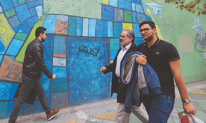 """Tehran: People walk past colourful walls here on Monday. Iran's President Hassan Rouhani said the Islamic republic  """"will proudly bypass sanctions"""" by the United States that took effect on Monday targeting the country's oil and financial sectors.—AFP"""