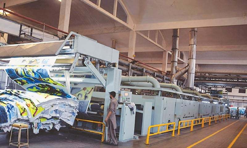 A worker operates a machine at a textile factory in Faisalabad.—File photo