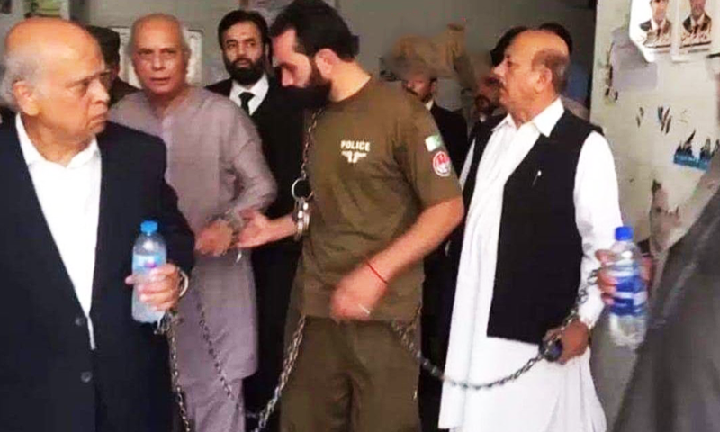 Ex-vice chancellor Dr Mujahid Kamran and four other former administrative officials of the Punjab University (PU) being taken away by NAB officials in handcuffs. —DawnNewsTV/file