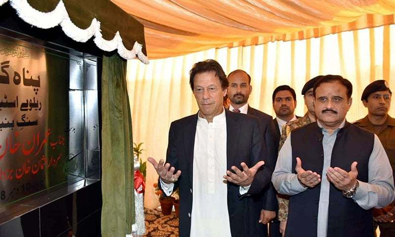 Prime Minister Imran Khan offering a prayer after unveiling the  plaque of the shelter project during a ceremony held at Lahore Railway Station. —APP