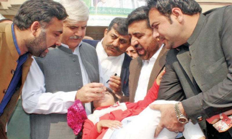 Chief Minister Mahmood Khan administers polio drops to a child in Peshawar on Monday. — Online