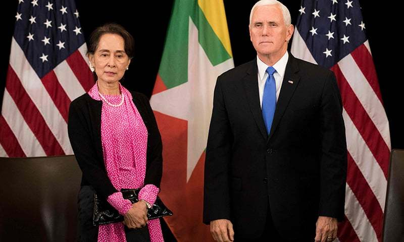 US Vice President Mike Pence (R) and Myanmar State Counsellor Aung San Suu Kyi arrive for a bilateral meeting on the sidelines of the 33rd ASEAN summit in Singapore on Nov 14. — AFP