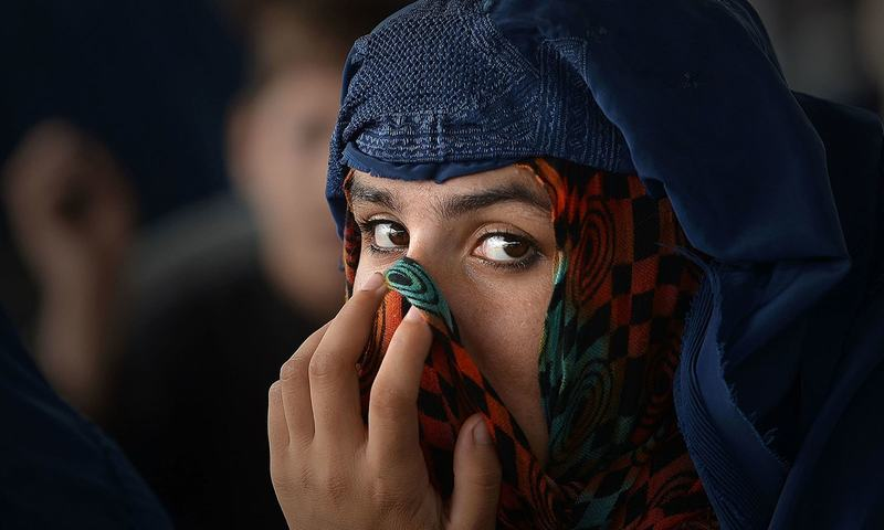 A refugee woman waits to board a truck at UNHCR repatriation centre near Peshawar.—AFP/File