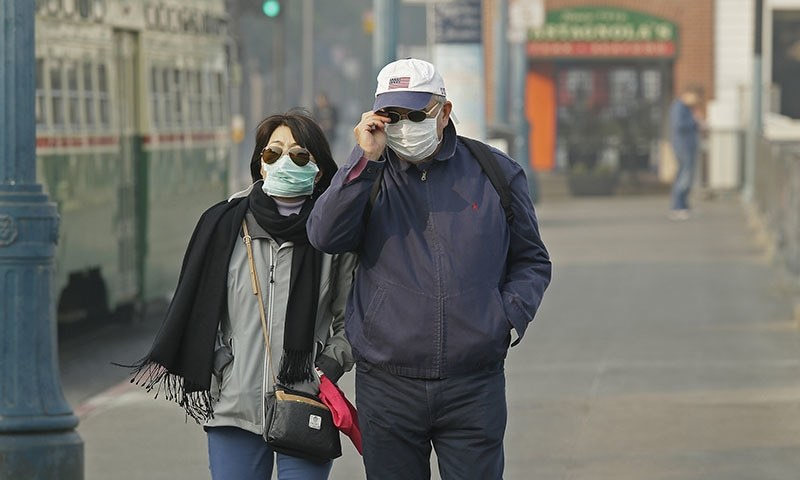 A couple wears masks while walking at Fisherman's Wharf through smoke and haze from wildfires on November 16, 2018, in San Francisco. — AP