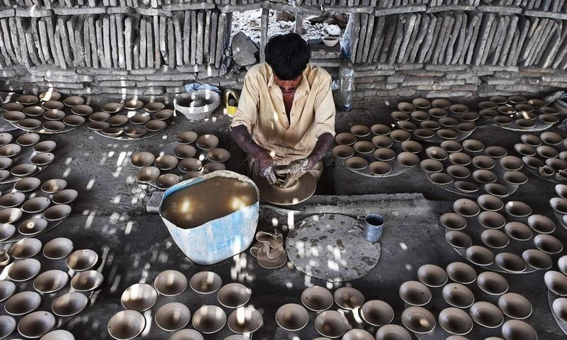 A Pakistani labourer makes clay dishes at a factory in Karachi on April 30, 2017. — AFP/File