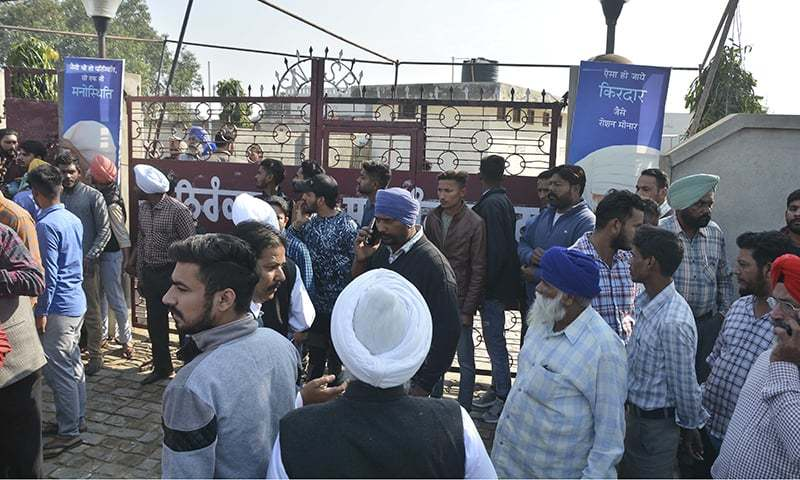 People gather outside after a blast at Nirankari Bhawan, a prayer hall in Adliwal village near Amritsar, India. — AP