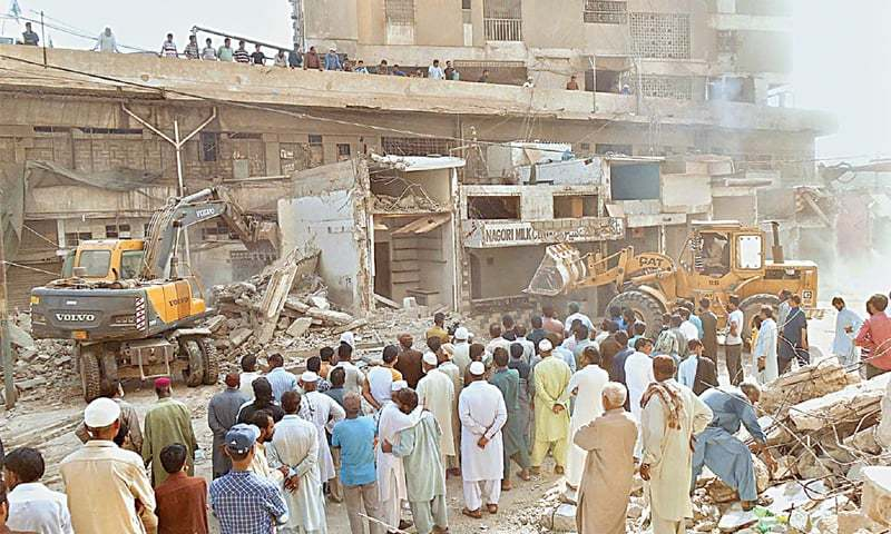 ONLOOKERS gather on Katrak Road near the Rainbow Centre in Saddar, where staff of the Karachi Metropolitan Corporation is demolishing illegally-constructed shops with heavy machinery on Sunday.—APP