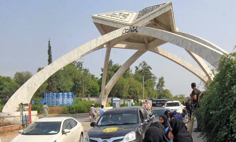 Police personnel stand at Quaid-i-Azam University (QAU) during crackdown against protesting students. —Dawn Archives