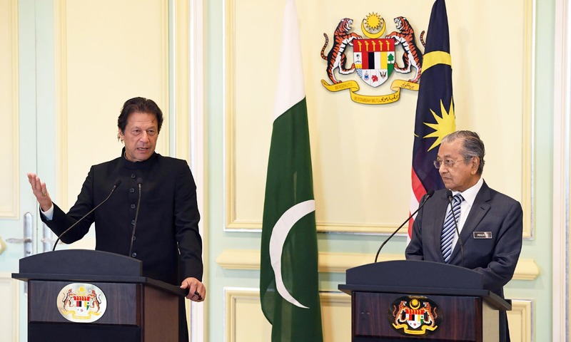PM Imran Khan (L) speaks as his Malaysian counterpart Mahathir Mohamad looks on during a joint press conference in Putrajaya. —AFP