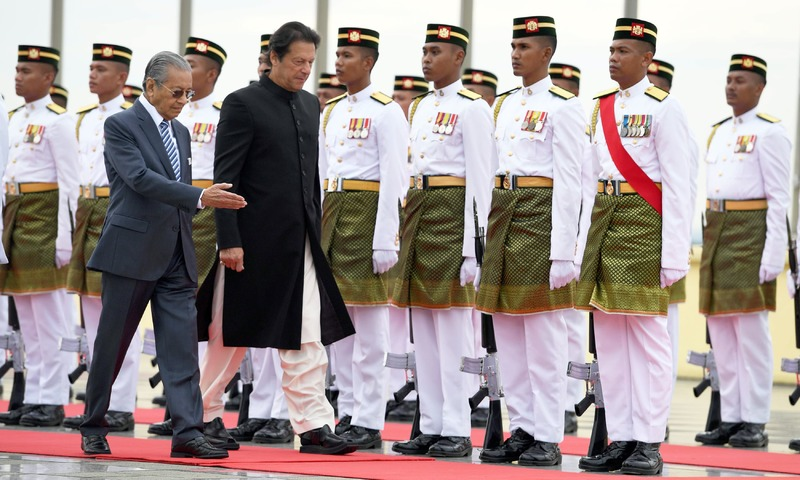 Malaysia's PM Mahathir Mohamad escorts his Pakistani counterpart Imran Khan during a welcoming ceremony in Putrajaya. —AFP