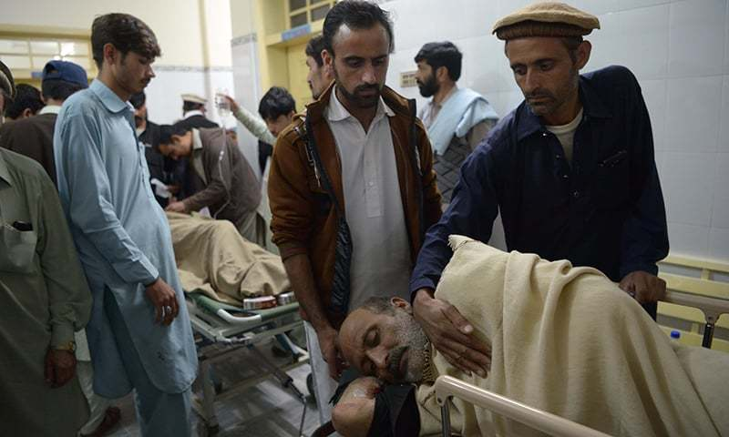 Relatives look over an injured bomb blast victim at a hospital. — AFP