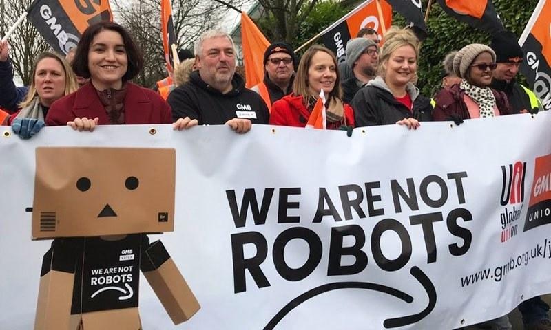 ملازمین نے ہم روبوٹ نہیں ہے کہ بینر اٹھا رکھے تھے—فوٹو: مشابیل