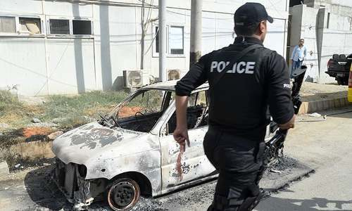 A police commando walks past a burned out vehicle outside the Chinese consulate after an attack in Karachi. — AFP/File