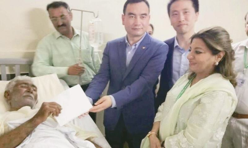 KARACHI: Chinese diplomat Liu Yuanli presents a cheque for Rs500,000 to a guard during a visit to Jinnah Post-Graduate Medical Centre on Sunday. The guard was injured in Friday's attack by militants on the Chinese consulate.—PPI