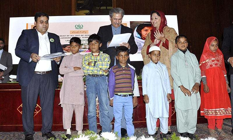 """Federal Minister for Education and Professional Training Shafqat Mahmood signing enrolment documents of six children at the launching ceremony of """"Parho, Aagay Barho"""" at National Library. —APP"""