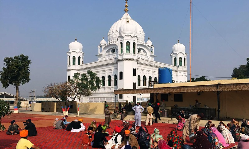 Sikh Pilgrims sit in front of Kartarpur Gurdwara Sahib before the groundbreaking ceremony of the Kartarpur Corridor. —AFP