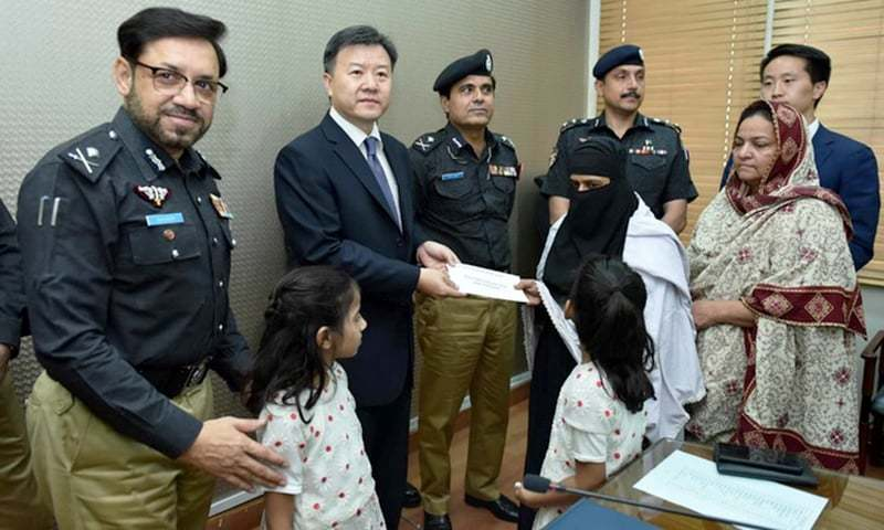 Consul General Wang Yu distributing the sum among the heirs of the deceased. —Photo courtesy Sindh police