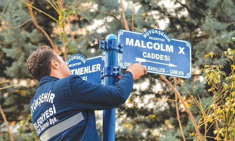 "Ankara: A municipality worker hangs the road sign for ""Malcolm X Avenue"", where the new US embassy is being built.—AFP"