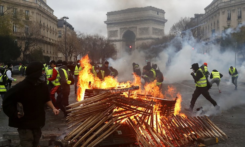 Demonstrators run by a burning fire near the Arc de Triomphe during a demonstration Saturday, Dec.1, 2018 in Paris. ─ AP