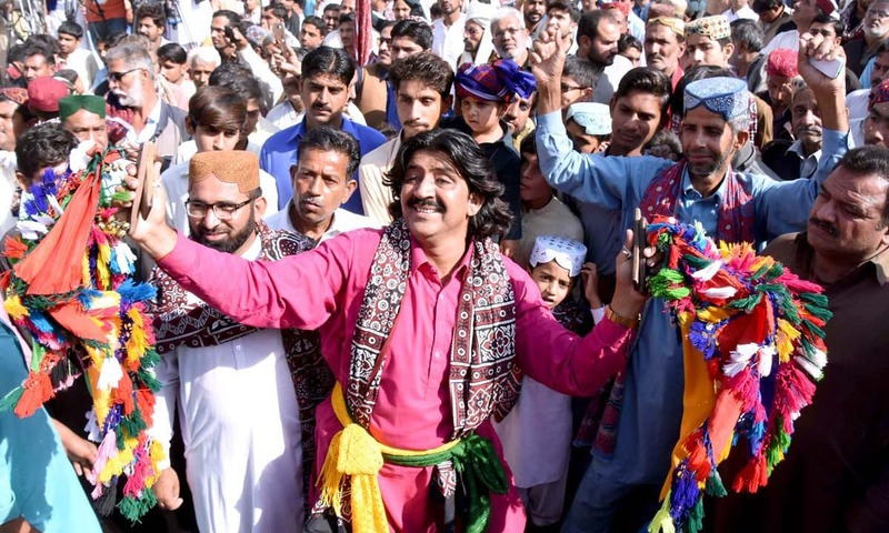 Folk artists perform in a rally held to mark the Sindhi Culture Day in Larkana. —APP