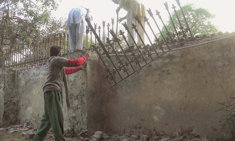 LAHORE: Labourers taking down the iron fence from the boundary wall of Punjab Governor House on Sunday before the planned demolition of the wall. The wall will be replaced with an iron grille to give a clear view of the majestic colonial-era building to the public. The exercise, which will cost the exchequer around Rs60 million, is being carried out on the instruction of Prime Minister Imran Khan.—Aun Jafri / White Star     Report on Page 2