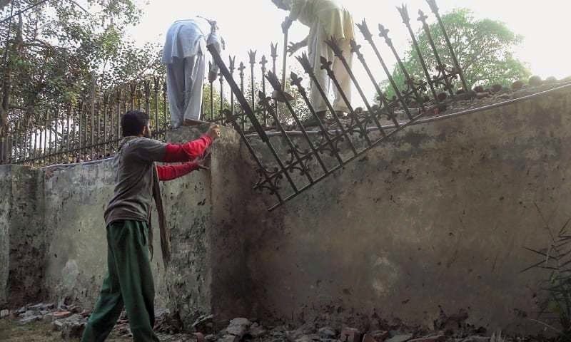 Labourers taking down the iron fence from the boundary wall of Punjab Governor House on Sunday before its planned demolition. — Aun Jafri / White Star