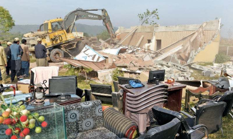 A CDA team demolishes a structure outside the entrance of Bahria Enclave on Monday. — Photo by Tanveer Shahzad