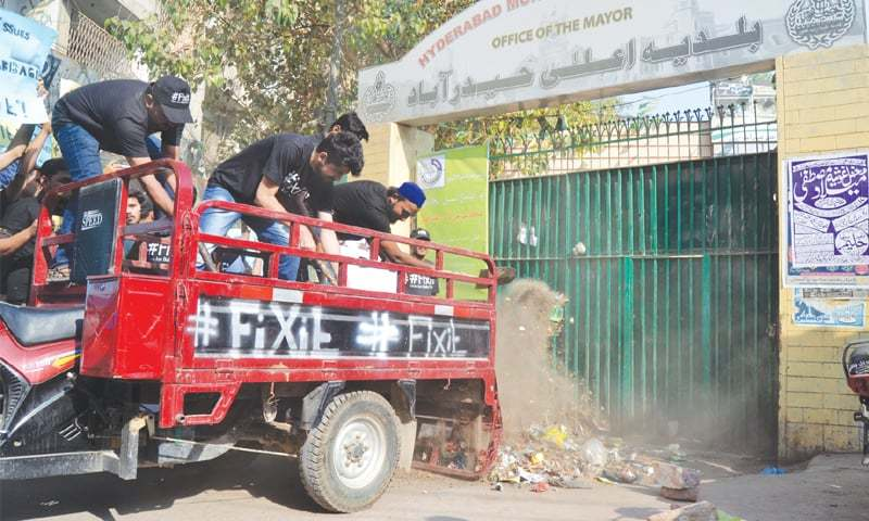 Garbage being dumped outside the Hyderabad mayor's office on Tuesday.—Dawn