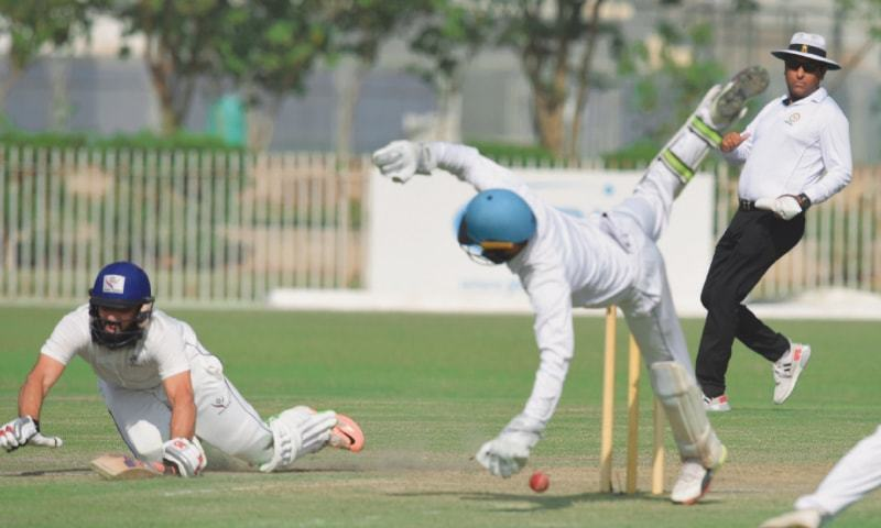 KARACHI: SNGPL captain Misbah-ul-Haq dives into the crease as HBL wicket-keeper Jamal Anwar fails to gather the ball cleanly during the Quaid-i-Azam Trophy National Cricket Championship final at the UBL Sports Complex on Wednesday.—Tahir Jamal / White Star