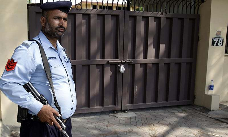 In this Sunday, June 14, 2015 file photo, a police officer stands guard outside a sealed office of international aid group Save the Children, in Islamabad. — AP