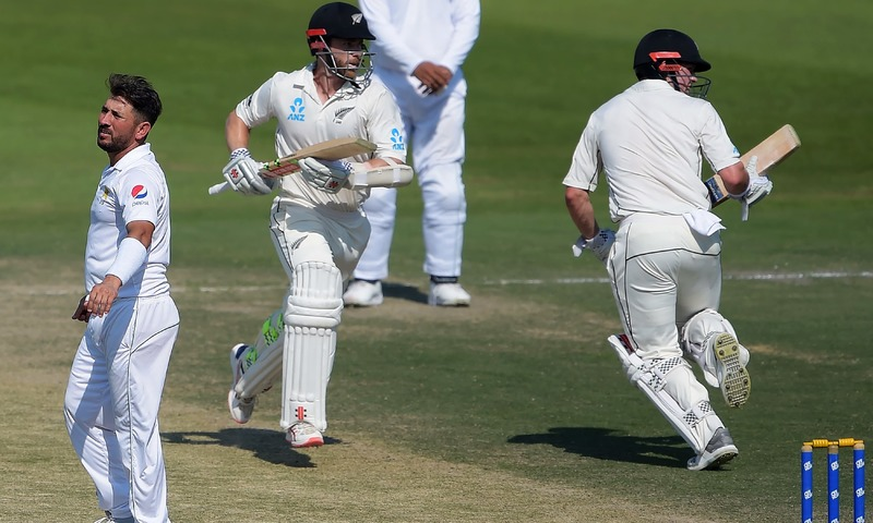 Kane Williamson and Henry Nicholls run between wickets next to Yasir Shah during the fourth day of the final Test match. —AFP