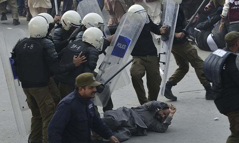 Policeman beat a supporter of arrested PML-N President Shahbaz Sharif on his arrival at an accountability court in Lahore. — AFP