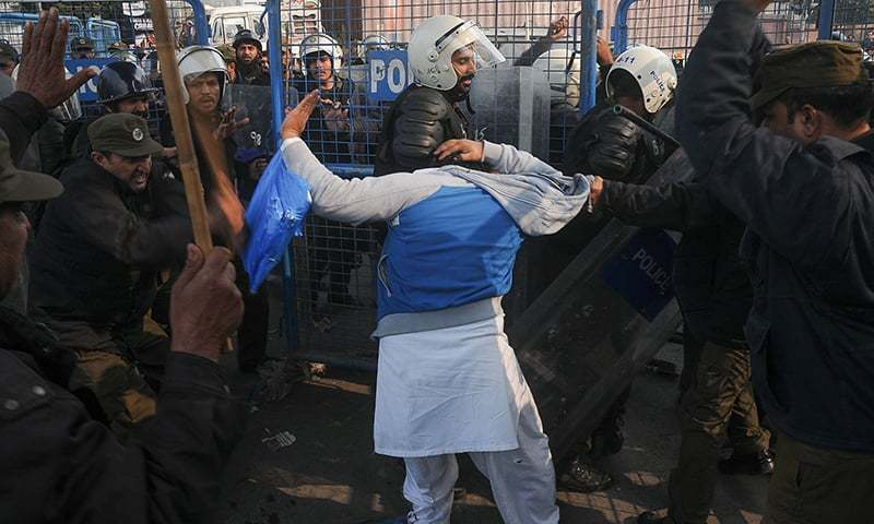 Policeman beat a supporter of arrested PML-N President Shahbaz Sharif on his arrival at an accountability court in Lahore. —AFP