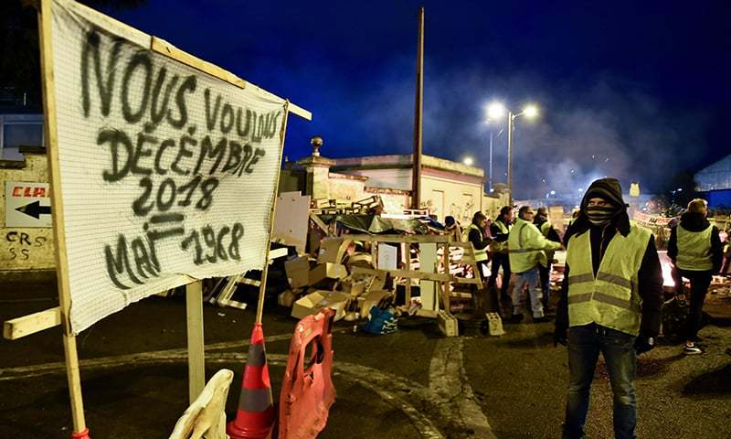 "A yellow vest protestor (gilets jaunes) looks at a banner reading ""We want December 2018 = May 1968"" on a baricade blocking the access to the oil depot, on December 6, 2018, in Le Mans, northwestern France. — AFP"