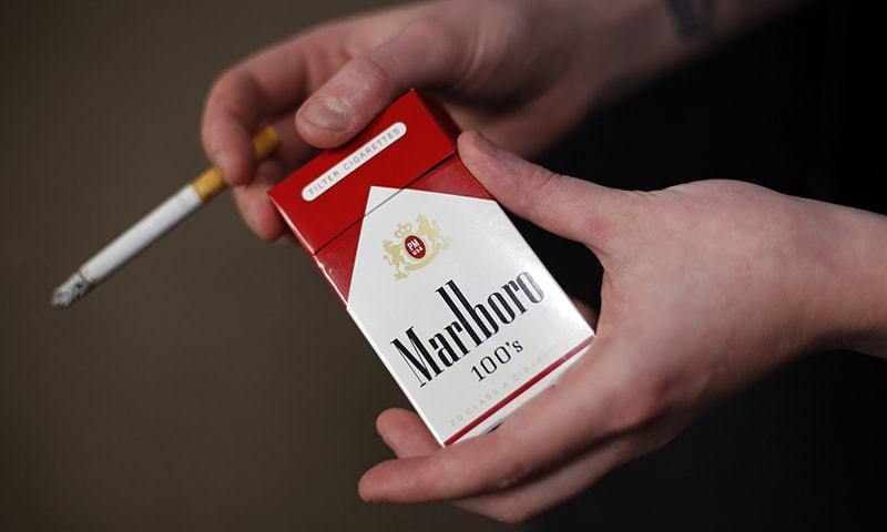 In this July 17, 2015, file photo, store manager Stephanie Hunt poses for photos with a pack of Marlboro cigarettes, an Altria brand, at a Smoker Friendly shop in Pittsburgh.  — AP