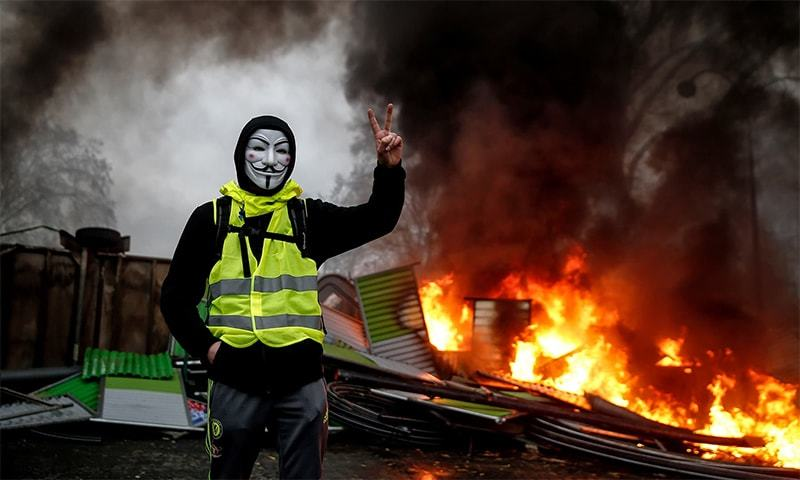 A protester wearing a Guy Fawkes mask makes the victory sign near a burning barricade. —AFP/File
