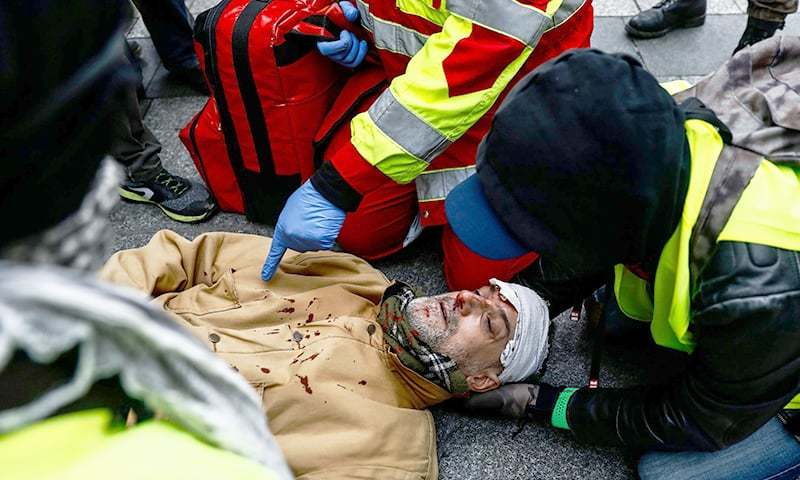A Firefighter Helps An Injured Man Near The Champs Elysees Avenue In Paris On December 8