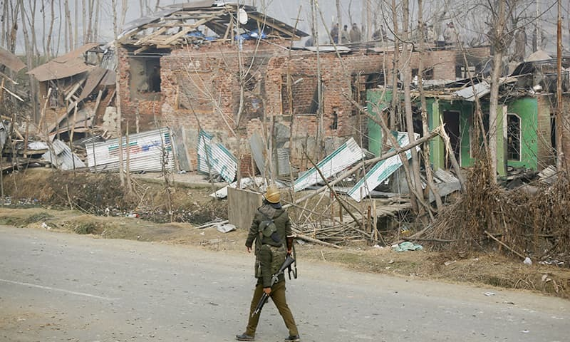 Indian policemen walk past the houses damaged in a gunbattle in the Mujagund area some 25 Kilometers from Srinagar. ─ AP