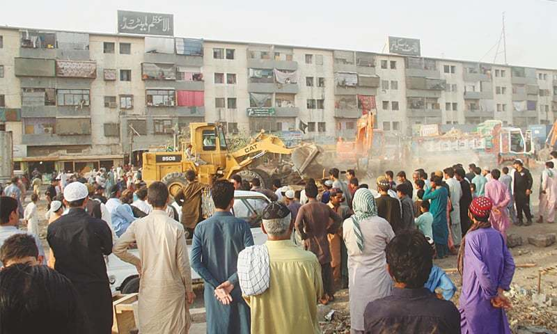PEOPLE look on as heavy machinery demolishes encroachments in the Sohrab Goth area on Monday. Officials said the operation went off smoothly.—Online