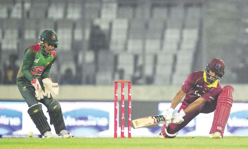 DHAKA: West Indies' opener Shai Hope plays a shot as Bangladesh wicket-keeper Mushfiqur Rahim looks on during the second ODI at the Sher-e-Bangla National Stadium on Tuesday.—AFP