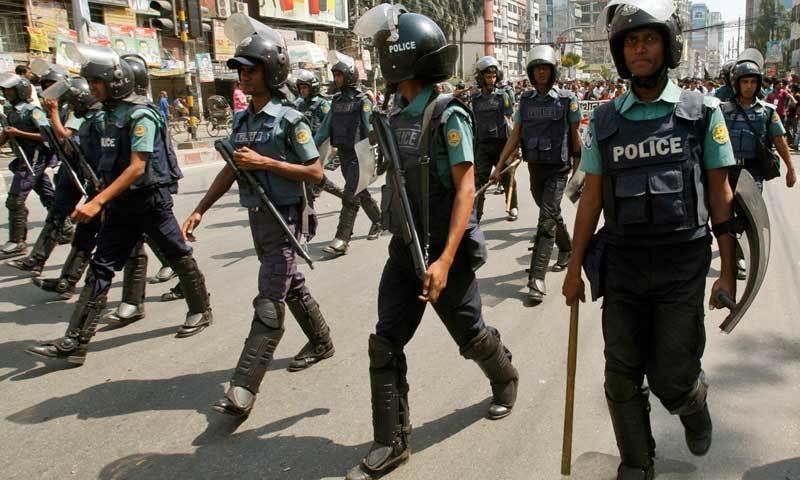 Riot policemen escort Bangladeshi protesters. — AP