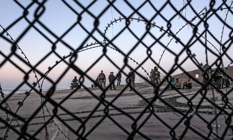 Central American migrants —travelling in a caravan — sit next to US border patrol officers after crossing the Mexico-US border fence to San Diego County, as seen from Playas de Tijuana, Baja California state, Mexico on December 13, 2018.  — AFP