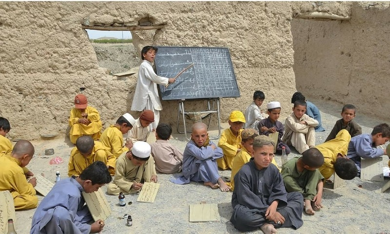 Children sit on the floor at an open-air school in Balochistan. — Asmatullah Khan/File