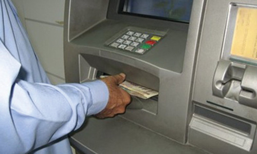 A file photo of cash being withdrawn from an ATM.