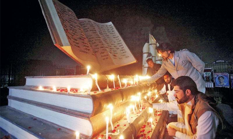 Members of civil society light candles at the monument of martyrs of Army Public School, Peshawar, on Saturday. — White Star