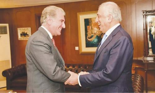 Foreign Minister Shah Mehmood Qureshi and US special representative Zalmay Khalilzad shake hands ahead of a meeting. — File photo